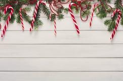 Предпосылка рождества с конфетами и границей ели на древесине Стоковое Фото
