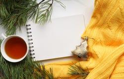 Предпосылка рождества с чашкой чаю, тетрадью, ветвями сосны с большими иглами и желтым свитером Взгляд сверху Стоковая Фотография