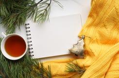 Предпосылка рождества с чашкой чаю, тетрадью, ветвями сосны с большими иглами и желтым свитером Взгляд сверху Стоковое Фото