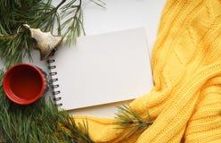 Предпосылка рождества с чашкой чаю, тетрадью, ветвями сосны с большими иглами и желтым свитером Конец-вверх взгляд сверху Стоковое фото RF
