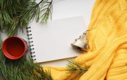 Предпосылка рождества с чашкой чаю, тетрадью, ветвями сосны с большими иглами и желтым свитером Конец-вверх взгляд сверху Стоковые Изображения RF