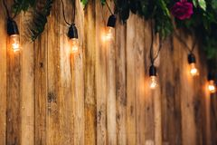 Предпосылка свадьбы доск, украшенная с электрическими лампочками и цветками стоковое фото