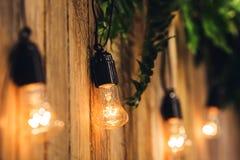Предпосылка свадьбы доск, украшенная с электрическими лампочками и цветками стоковые фотографии rf