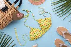 Предпосылка с листьями ладони, шляпа лета моды, бикини, темповые сальто сальто, сумка на светлой пастельной голубой предпосылке,  стоковое фото