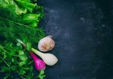 Предпосылка с травами, салат, лук, чеснок, на черном затрапезном t Стоковая Фотография RF