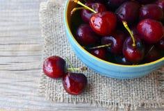 Предпосылка ткани мешковины Ягоды вишни на старом деревянном столе Плодоовощ лета или здоровая концепция еды Стоковое фото RF
