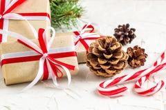 Предпосылка украшений рождества или Нового Года с конусами сосны, ветвями ели, подарочными коробками, и тросточками конфеты стоковое фото rf