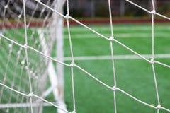 Предпосылка футбола или футбола сетчатая, взгляд от за цели с запачканным стадионом и тангаж поля Стоковые Фото