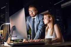 Предприниматели в офисе на ноче работая поздно стоковые изображения rf