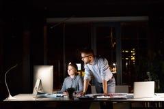 Предприниматели в офисе на ноче работая поздно Стоковое Изображение RF