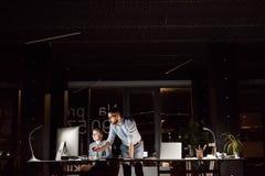 Предприниматели в офисе на ноче работая поздно Стоковые Изображения