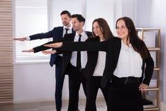 Предприниматели делая тренировку при протягиванные руки стоковое фото