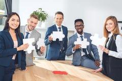 Предприниматели держа части головоломки стоковая фотография rf