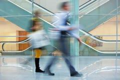 Предприниматели идя быстро с багажом вниз Hall в офисе стоковое фото rf