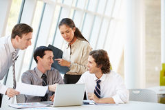 Предприниматели имея встречу вокруг таблицы в самомоднейшем офисе стоковое изображение rf