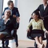 Предприниматели имея катание потехи на стульях и смеясь над в offic стоковое изображение rf