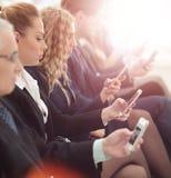 Предприниматели используя технологию в занятой зоне лобби офиса стоковые фото