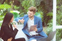 Предприниматели используя цифровой планшет работая в современном офисе, сыгранности планирования людей дела 2 говоря с компьтер-к Стоковая Фотография RF