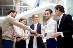 Предприниматели используя цифровую таблетку совместно в офисе Стоковые Фотографии RF