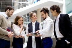 Предприниматели используя цифровую таблетку совместно в офисе Стоковая Фотография