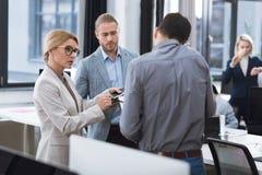 предприниматели обсуждая конторскую работу Стоковое Изображение
