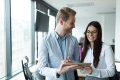 Предприниматели обсуждая пока использующ цифровую таблетку в офисе стоковое изображение rf