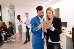 Предприниматели обсуждая пока использующ цифровую таблетку в офисе стоковая фотография rf