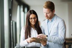 Предприниматели обсуждая пока использующ цифровую таблетку в офисе стоковое изображение