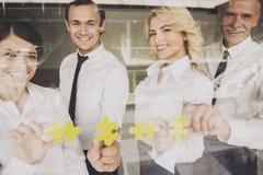 Предприниматели положили части головоломки на стеклянную дверь Стоковые Фото