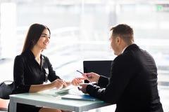 Предприниматели сидя на таблице и подписывая контракт на офисе Стоковое Изображение RF