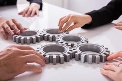 Предприниматели соединяя шестерни на столе стоковые фотографии rf
