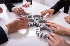 Предприниматели соединяя шестерни на столе стоковые изображения rf