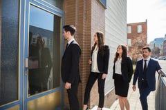 Предприниматели стоя внешнее офисное здание стоковая фотография