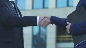 Предприниматели тряся руки твердо, успешное сотрудничество в продвижении дела сток-видео