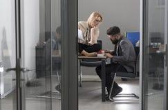 Предприниматели человека и женщины писать идеи дела на бумаге Инвесторы дела обсуждая идеи дела в офисе стоковое изображение rf
