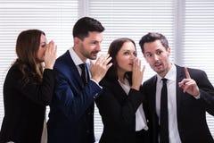 Предприниматели шепча в мужское ухо ` s коллеги стоковые изображения