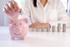 Предприниматель вводя монетки в копилку со стогом монеток над столом стоковые фотографии rf