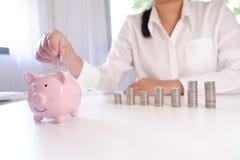 Предприниматель вводя монетки в копилку со стогом монеток над столом стоковые изображения