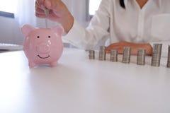 Предприниматель вводя монетки в копилку со стогом монеток над столом стоковые фото