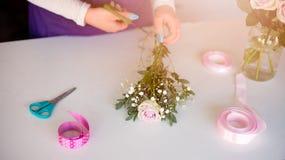 Предприниматель женщины магазина флориста подготавливая букет розовых роз Стоковые Изображения