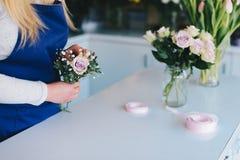 Предприниматель женщины магазина флориста подготавливая букет розовых роз Стоковые Изображения RF