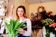 Предприниматель женщины магазина флориста подготавливая букет розовых тюльпанов Стоковое Изображение RF