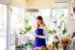 Предприниматель женщины магазина флориста принимая заказы онлайн стоковые изображения rf
