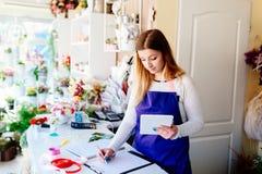 Предприниматель женщины магазина флориста принимая заказы онлайн стоковое изображение