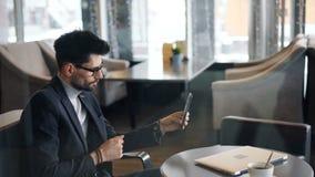 Предприниматель звоня видео- онлайн используя смартфон с камерой в кафе видеоматериал
