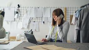 Предприниматель мелкого бизнеса приказывает ткань для магазина ` s портноя с мобильным телефоном и работает с компьтер-книжкой го сток-видео
