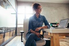 Предприниматель молодой женщины на ее столе стоковые изображения