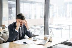 Предприниматель на бизнес-ланче на ресторане сидя около окна имея головную боль стоковые фото