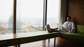 Предприниматель работая дома или в отключении Портрет взгляда со стороны красивого молодого бизнесмена сидя на кровати и использо акции видеоматериалы