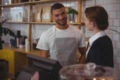 Предприниматель разговаривая с кельнером в кафе стоковая фотография
